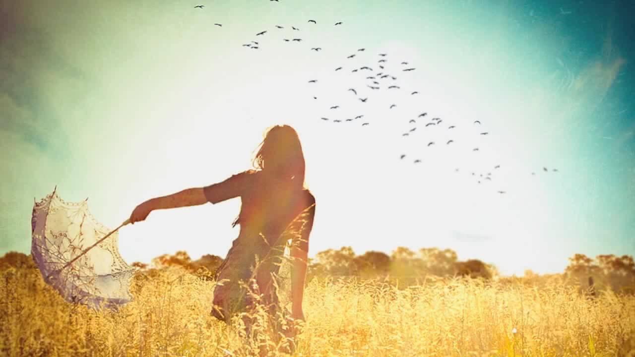 girl in field with birds and sunshine